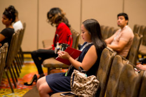 Girl taking notes at a 2018 USCA Panel